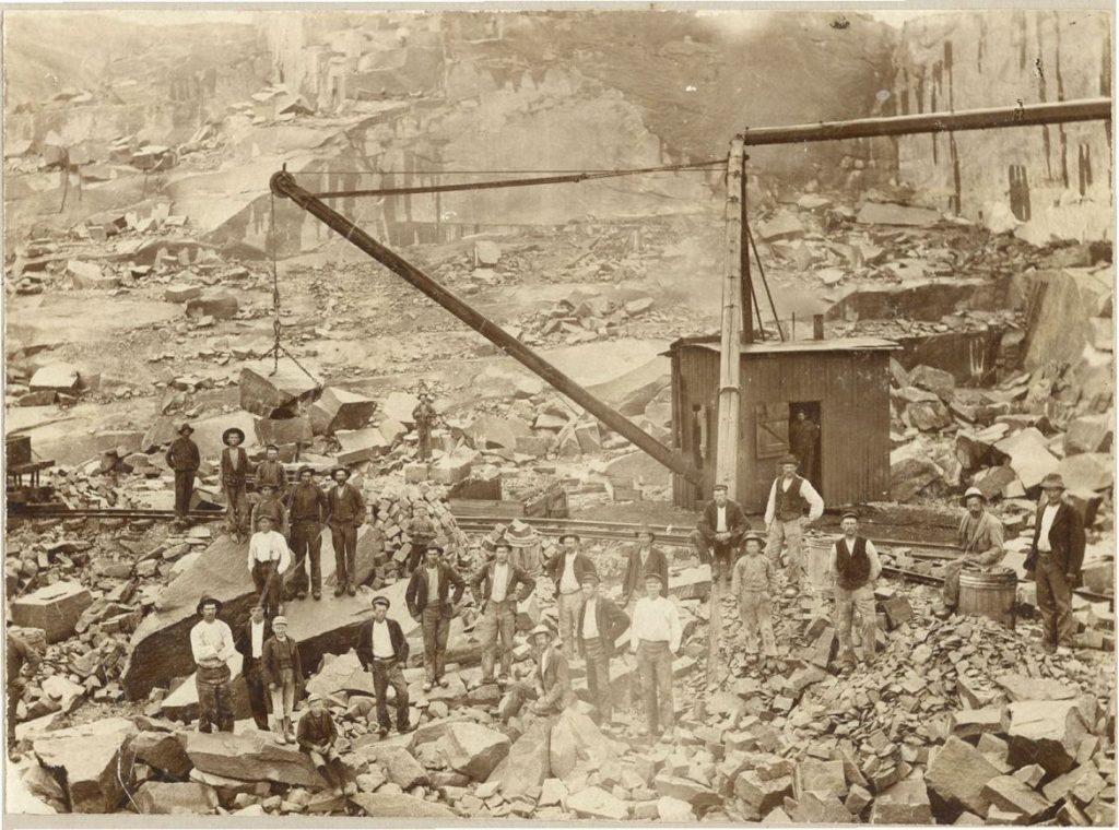 Gruppbild på stenhuggare i stenbrott. Med på bilden finns även en kran.