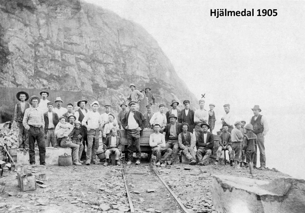 Gruppbild på stenhuggare. J. Nilsson är markerad med ett X på fotot. På bilden finns även en vagn som går på räls.