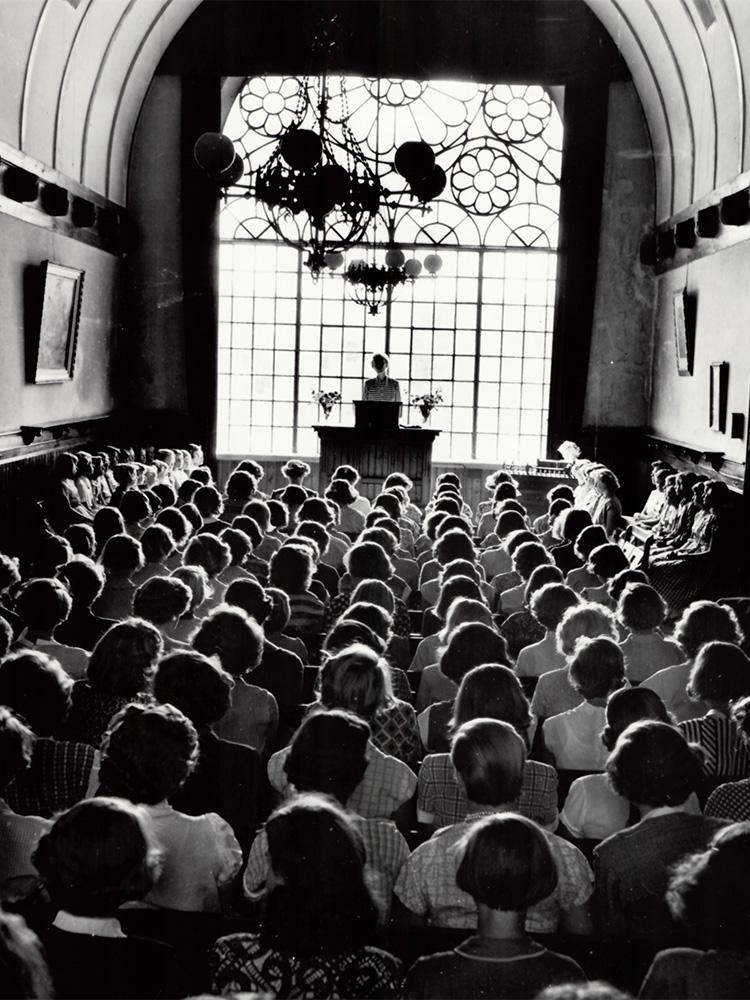 Stor sal med närmare 100 tal kvinnliga elever framför en lärare/rektor. Stort fönster i bakgrunden.