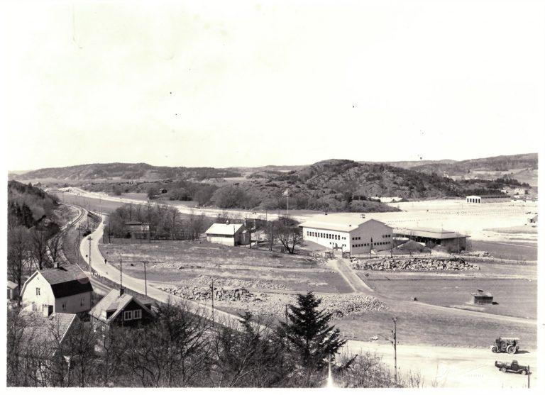 Vy med hus, väg, fält och större byggnad som är folkets park Uddevalla.