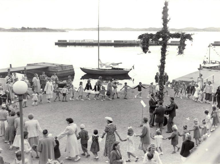 Vuxna och barn dansar kring midsommarstången. 3 mannaorkester står vid midsommarstången. Segelbåt och Gullmarn? i bakgrunden.