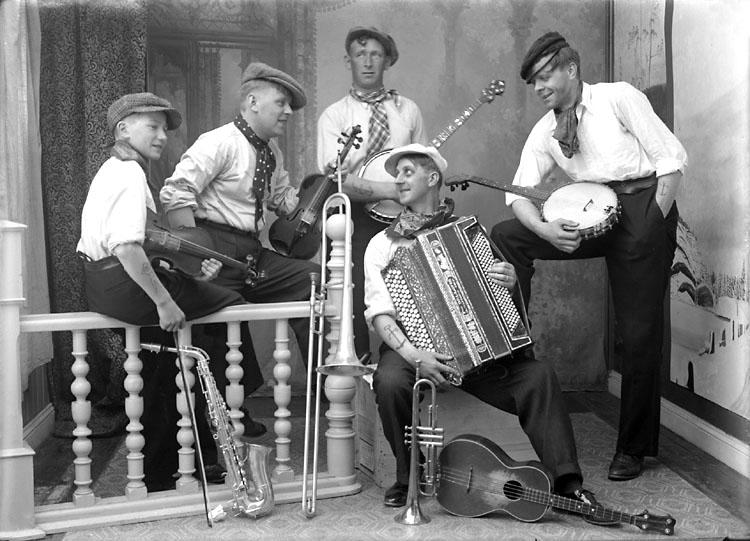 5 stycken musiker med dragspel, banjo och fiol. Framför på golvet finns saxofon, trombon, trumpet och ett fyrsträngat instrument.