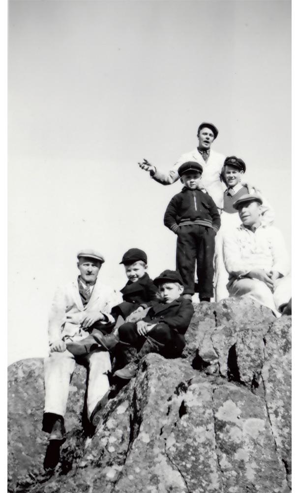 3 stycken målare och 4 barn som klättrat upp i berg.