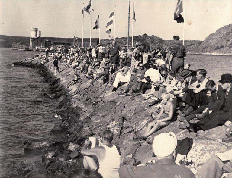 Publik och flaggor på stenpir i Uddevallas yttre hamn.