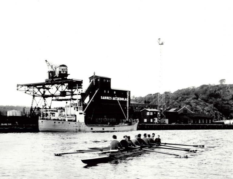 8 mannaroddbåt med styrman i Uddevalla hamn. I bakgrunden fraktfartyg, Skansberget och byggnad med bokstäver Sannes aktiebolag.
