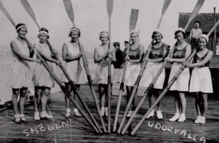 Smögen och Uddevallas kvinnliga roddlag. 8 damer som håller i var sin åra. I bakgrunden står en person och tittar på.