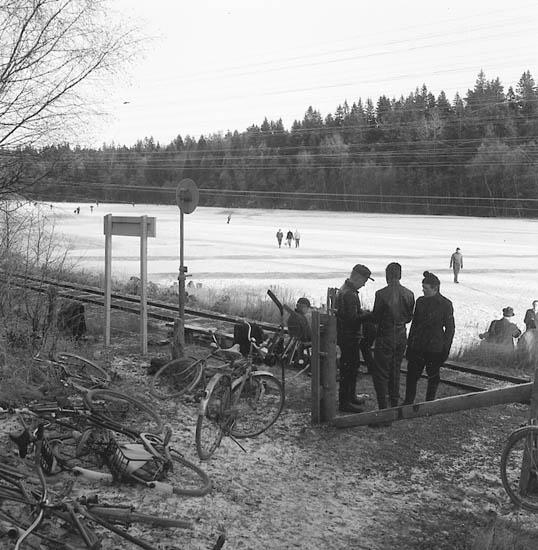Bjursjön Uddevalla vintertid. Cyklar i förgrunden och skridskoåkare i bakgrunden. Lelångens järnväg (Lelångenbanan) skär genom bilden.