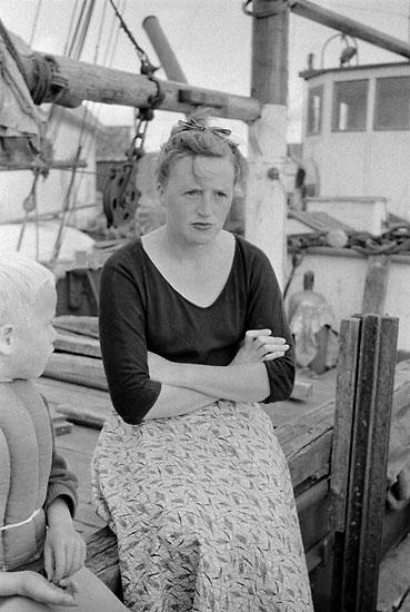 Fundersam kvinna och ett barn sittandes på däck på en fiskebåt.