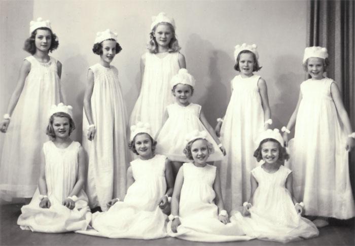 10 stycken flickor i 5-12 årsåldern. Klädda i vita klänningar och snöflingsmössor.