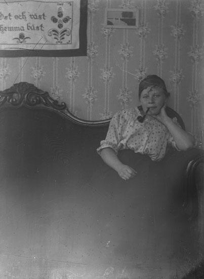 Piprökande kvinna sittande i soffa. På väggen finns en bonad med texten Öst och väst. Hemma bäst.