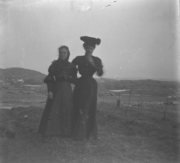 Två kvinnor ute o blåsten. En med hatt.