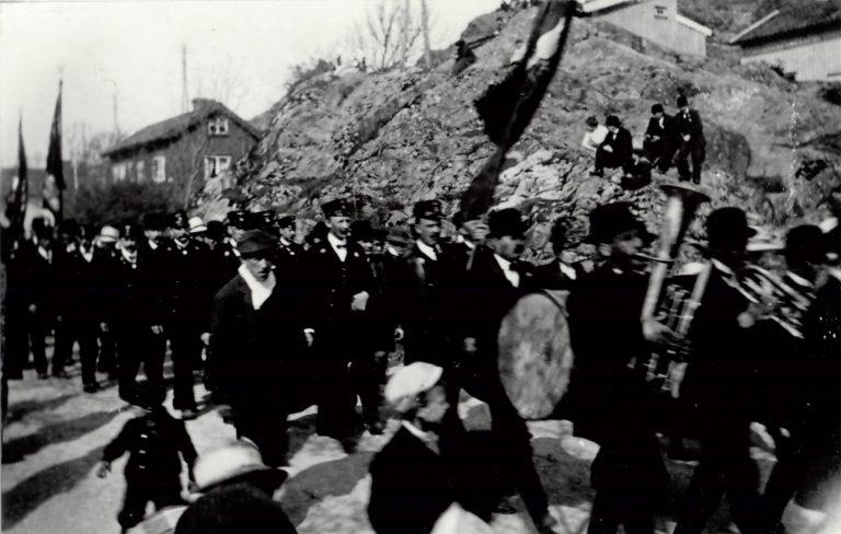 1 maj demonstration. Orkester längst fram. 4 åskådare sitter uppe i ett berg och ser på.
