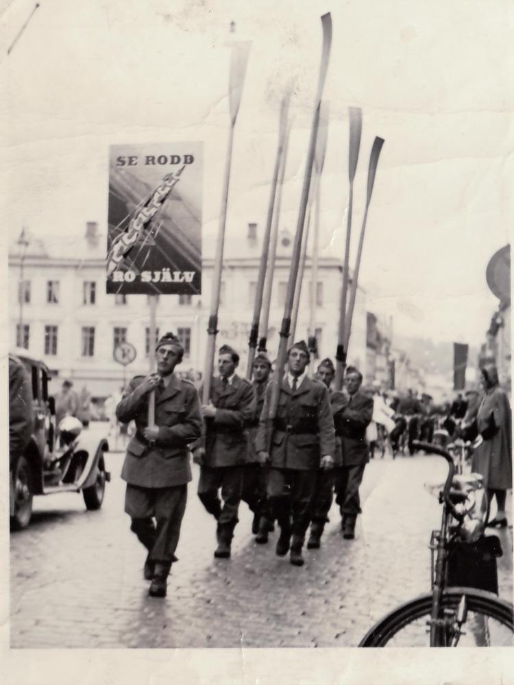 Uniformsklädda män som gör reklam för rodd gåendes på Kungsgatan i Uddevalla. En med plakat resten med åror.