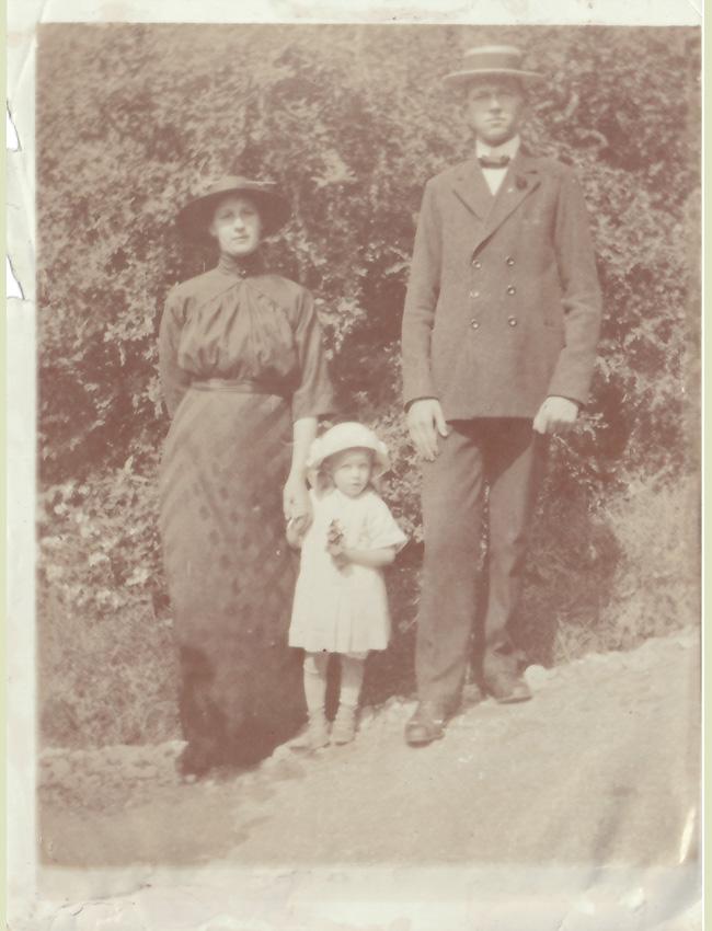 Finklädd familj med ett barn. Äldre foto.