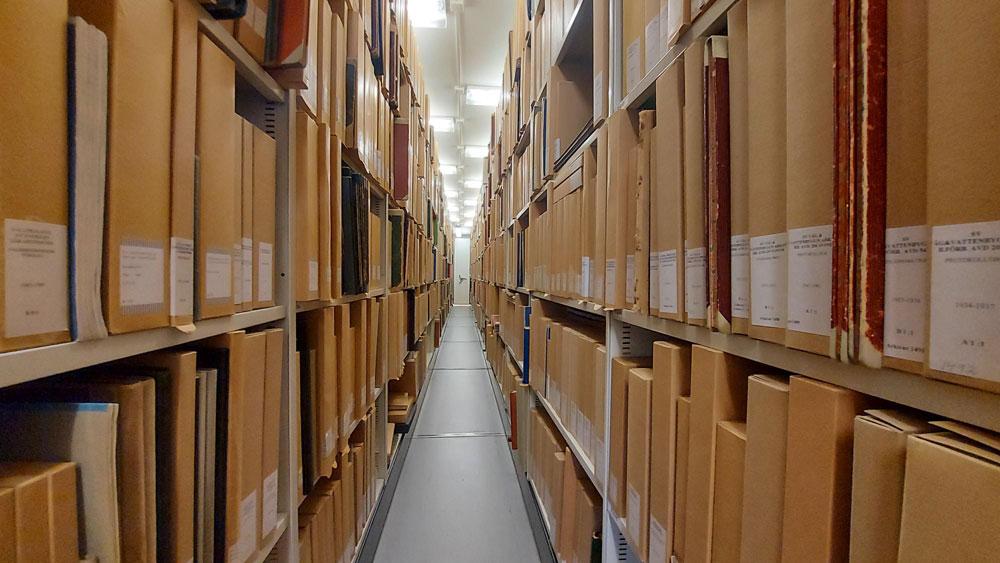 Vy längs arkivhyllor i ett arkiv.