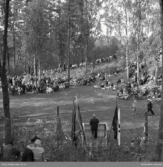 Svartvitt foto föreställande en person som talar inför andra. På bilden syns människor sitta i en grässlänt under några björkar.