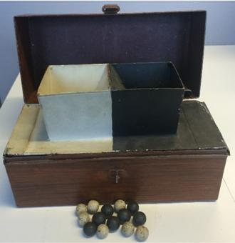 Tvådelad trälåda. En vit och en svart del. Framför lådan ligger svarta och vita kulor.