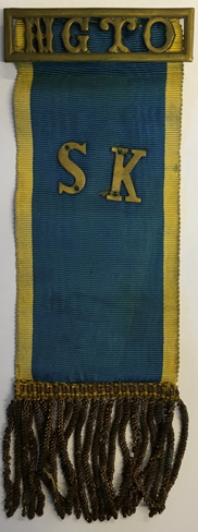 Bandregalia. Överst guldfärgad text NGTO på blå botten. Under detta guldfärgad text SK på blå botten. Längst ner fransar.